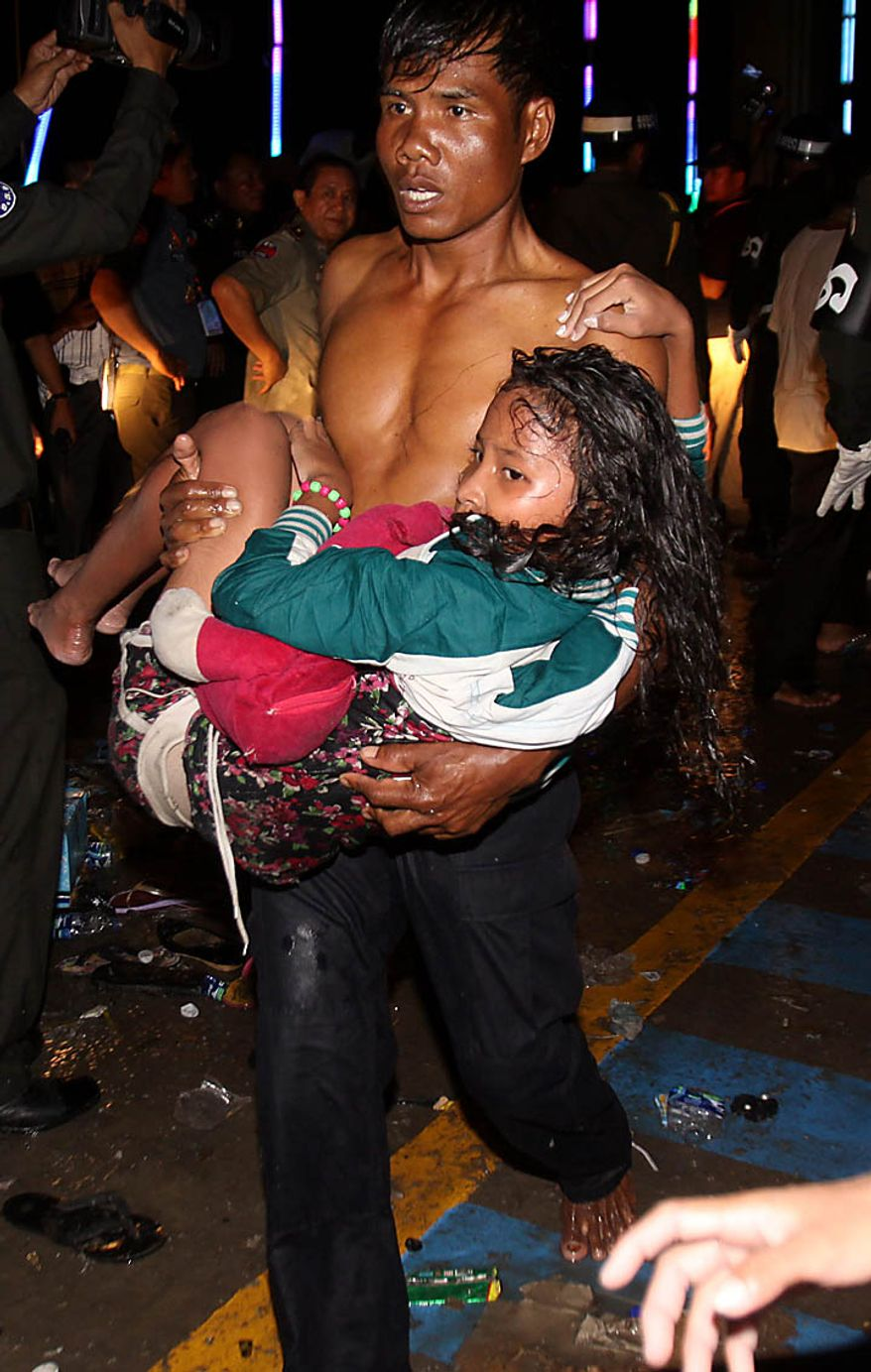 An injured Cambodian is carried by a another visitor after a  stampede onto a bridge at an accident site during the last day of celebrations of the water festival in Phnom Penh, Cambodia, Monday, Nov. 22, 2010. Thousands of people celebrating a water festival on a small island in a Cambodian river stampeded Monday evening, killing many people, a hospital official said. Hundreds more were hurt as the crowd panicked and pushed over the bridge to the mainland. (AP Photo/Heng Sinith)