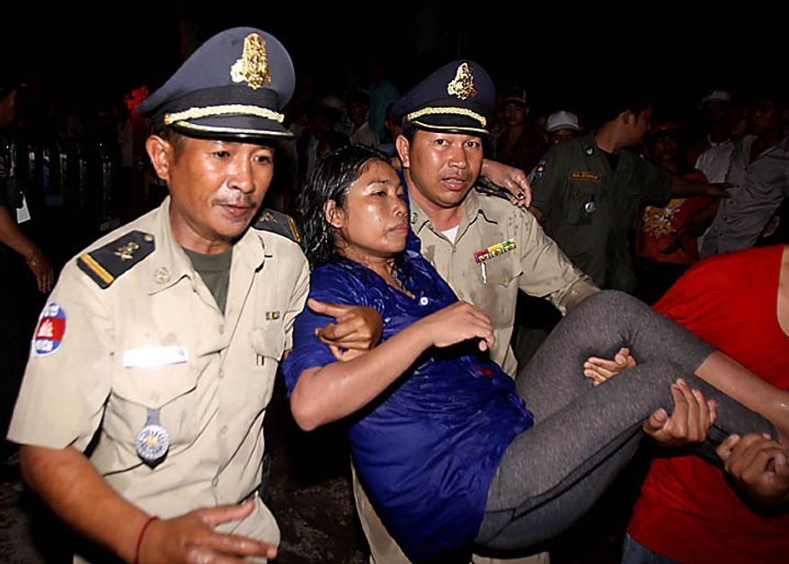 An injured visitor is carried by Cambodian police and another visitor after a stampede onto a bridge at an accident site during the last day of celebrations of the water festival in Phnom Penh, Cambodia, Monday, Nov. 22, 2010. Thousands of people celebrating a water festival on a small island in a Cambodian river stampeded Monday evening, killing many people, a hospital official said. Hundreds more were hurt as the crowd panicked and pushed over the bridge to the mainland. (AP Photo/Heng Sinith)