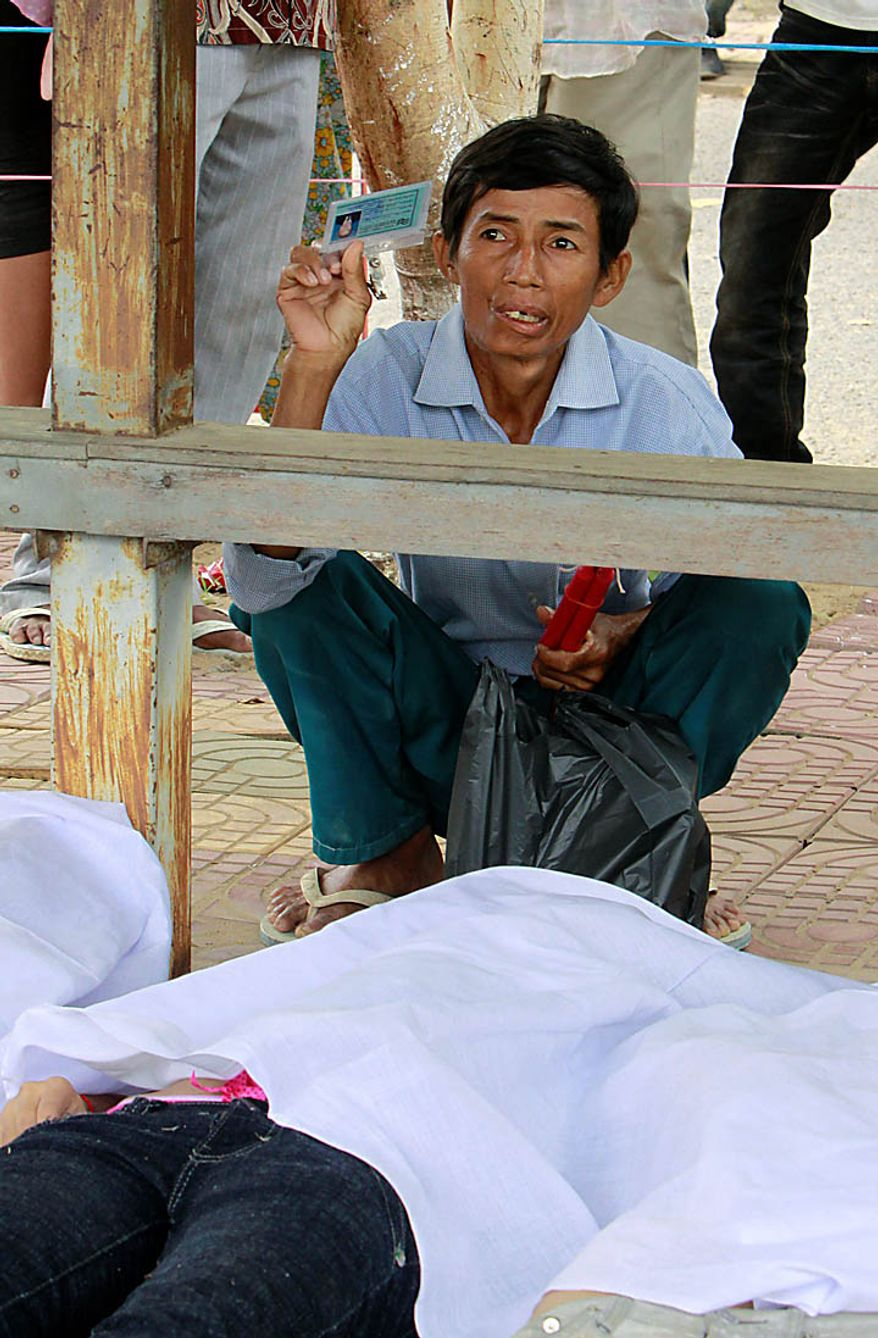A Cambodian relative of a stampede victim shows the dead's identification card at Preah Kossamak Hospital in Phnom Penh, Cambodia, Tuesday, Nov. 23, 2010. Thousands of people stampeded during a festival in the Cambodian capital, leaving over three hundred dead and scores injured in what the prime minister called the country's biggest tragedy since the 1970s reign of terror by the Khmer Rouge. (AP Photo/Heng Sinith)