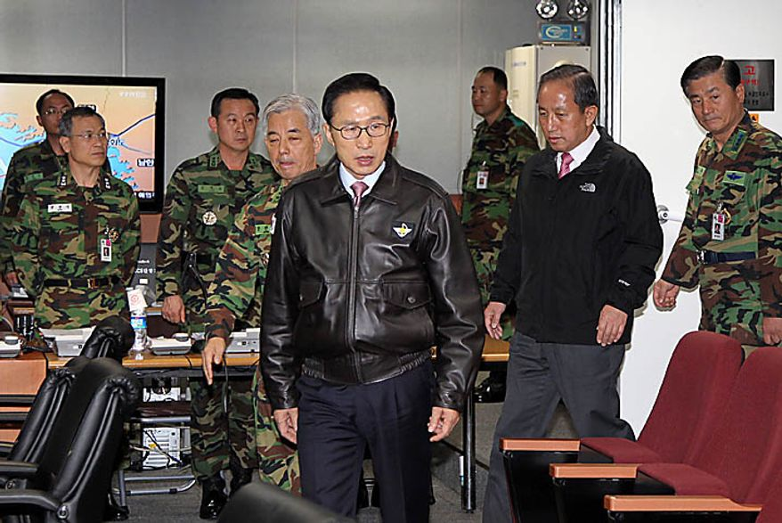 South Korean President Lee Myung-bak, center, arrives with Defense Minister Kim Tae-young, second right, at the Joint Chiefs of Staff as the military was put on top alert after North Korea's artillery attack on South Korean island of Yeonpyeong, in Seoul, South Korea, Tuesday, Nov. 23, 2010. (AP Photo/Yonhap)