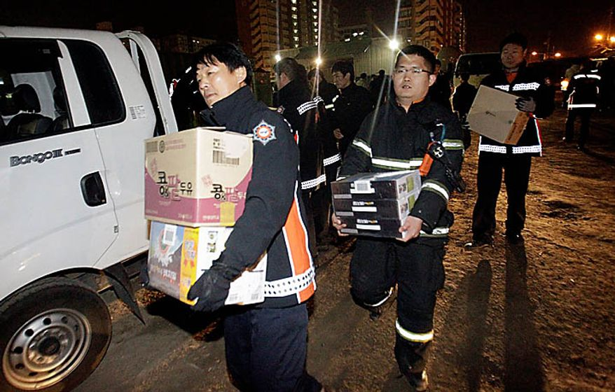 South Korean firefighters carry foods as they get on a boat for Yeonpyeong Island at a port in Incheon, west of Seoul, South Korea, Tuesday, Nov. 23, 2010. North Korea shot dozens of rounds of artillery onto the populated South Korean island near their disputed western border Tuesday, military officials said, setting buildings on fire and prompting South Korea to return fire and scramble fighter jets. (AP Photo/ Lee Jin-man)