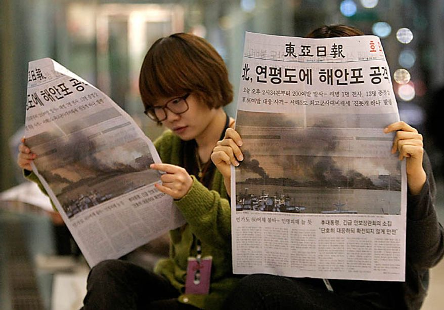 People read extra edition of a newpaper reporting that North Korea fired artillery onto a South Korean island, in Seoul, South Korea, Tuesday, Nov. 23, 2010. North Korea bombarded South Korea's Yeonpyeong island near their disputed western border Tuesday, setting buildings ablaze and killing at least one marine after warning the South to halt military drills in the area, South Korean officials said. (AP Photo/Ahn Young-joon)