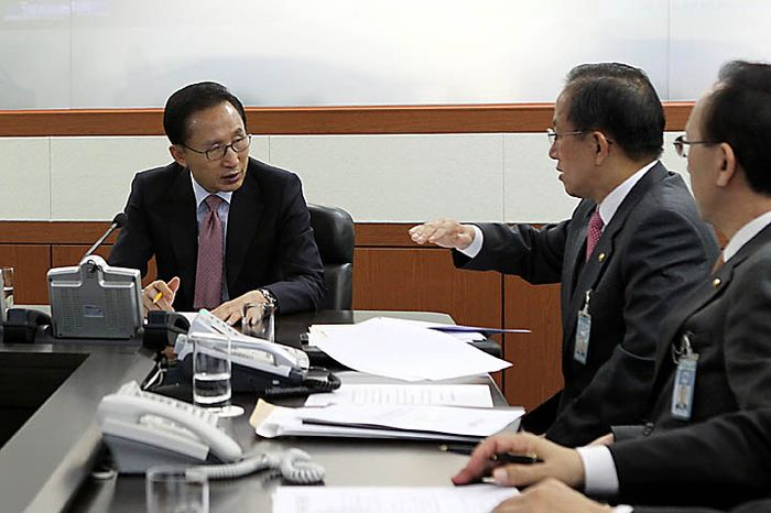 South Korean President Lee Myung-bak, left, talks with Defense Minister Kim Tae-young, second from right, during a security meeting at the presidential house in Seoul,  South Korea, Tuesday, Nov. 23, 2010. North Korea fired artillery barrages onto a South Korean island near their disputed border Tuesday, setting buildings alight and prompting South Korea to return fire and scramble fighter jets.  (AP