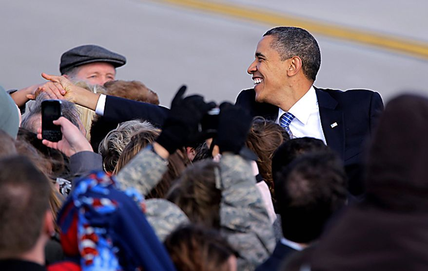 President Barack Obama reaches to shake hands with supporters after he arrived on Air Force One at Grissom Air Reserve Base in Peru, Ind., Tuesday, Nov. 23, 2010. (AP Photo/Michael Conroy)