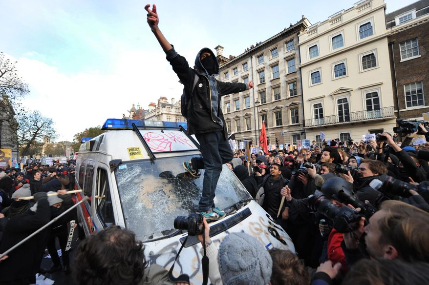 Student protesters target a police van during a demonstration against an increase in university tuition fees, in Westminster, central London Wednesday, Nov. 24, 2010. Several thousand British students protested Wednesday against government plans to triple tuition fees, two weeks after a similar demonstration sparked a small riot. (AP Photo/Anthony Devlin/PA)