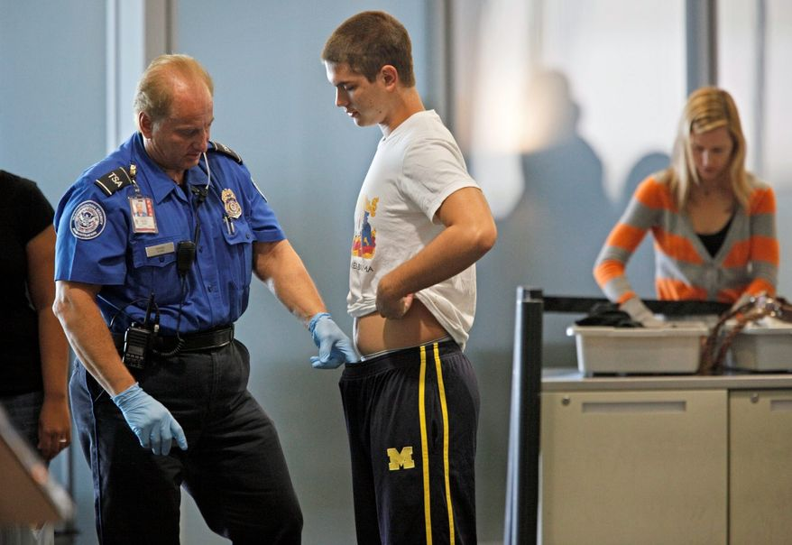 A passenger at Palm Beach International Airport is patted down by a TSA worker on Wednesday in West Palm Beach, Fla. Security lines moved quickly the day before Thanksgiving. (Associated Press)