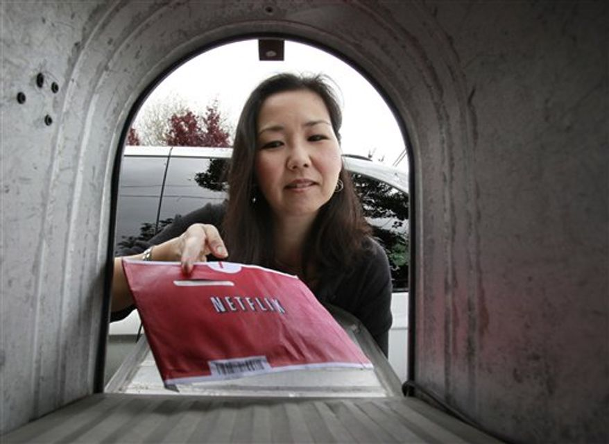 FILE - In this Nov. 24, 2010 file photo, a Netflix customer holds her movies she rented, at her home in Palo Alto, Calif. NetFlix Inc. releases quarterly financial earnings Wednesday, Jan. 26, 2011, after the market close.(AP Photo/Paul Sakuma, file)