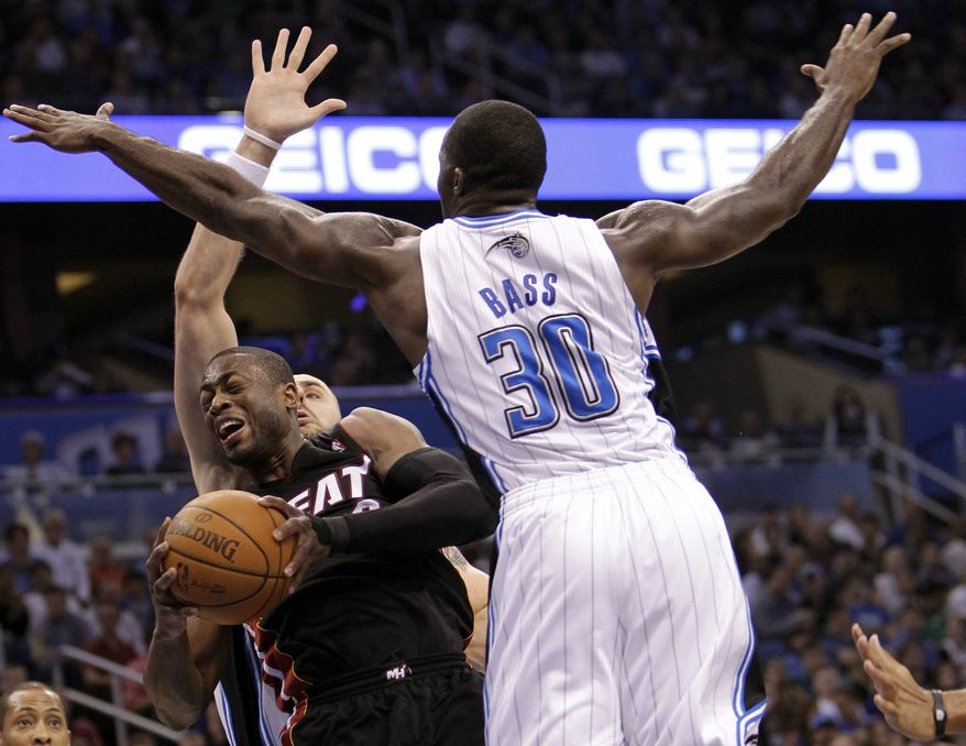 ASSOCIATED PRESS Miami Heat's Dwyane Wade, front left, tries to get off a shot between Orlando Magic's Marcin Gortat, back left, of Poland, and Brandon Bass (30) during the first half of an NBA basketball game in Orlando, Fla., Wednesday, Nov. 24, 2010.
