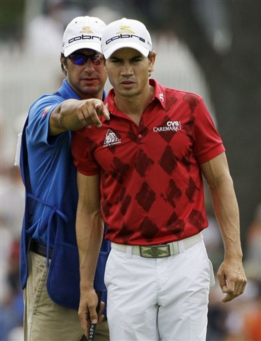 FILE - In this Aug. 13, 2009, file photo, Camilo Villegas, of Colombia, gets assistance from his caddie Brett Waldman, before putting on the ninth green during the first round of the 91st PGA Championship at the Hazeltine National Golf Club in Chaska, Minn. Waldman drew some quizzical looks at Q-school. After all, he caddies for Villegas, who made $3 million this year. Except Waldman wasn't working. Eight years after giving up on a pro career, the caddie has made it to the final stage of PGA Tour qualifying. (AP Photo/Morry Gash, File)