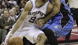 San Antonio Spurs' Tim Duncan, left, and Tony Parker, of France, right,  congratulate teammate Manu Ginobili, of Argentina, center, after was fouled as he scored late in the fourth quarter of an NBA basketball game against the Orlando Magic, Monday, Nov. 22, 2010 in San Antonio. San Antonio won 106-97.(AP Photo/Eric Gay)