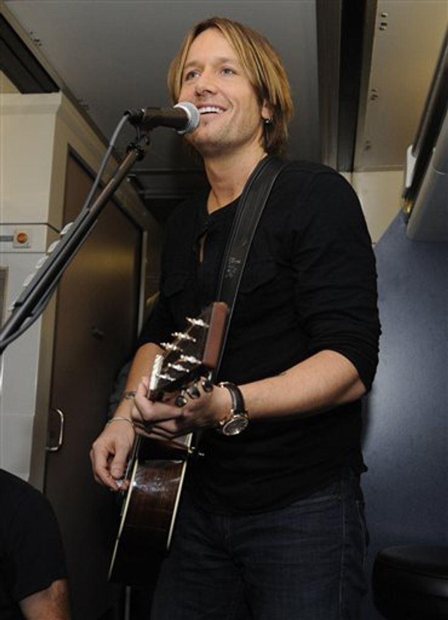FILE - A Nov. 16, 2010 file photo shows Keith Urban performing a free concert for winners of a contest conducted by his website, aboard an Amtrak train traveling from Philadelphia to New York. Urban is trying to make his fans and his family happy this summer. The multi-platinum country star is hitting the road June 16 on a 44-city arena tour in the U.S. with a schedule that gives him time to be with his wife, actress Nicole Kidman, and their 2-year-old daughter, Sunday Rose.(AP Photo/Henny Ray Abrams, File)