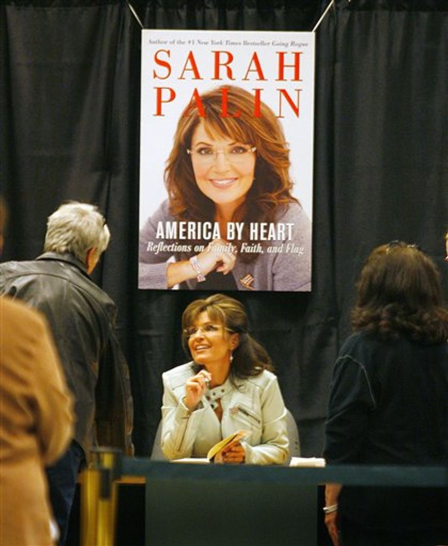 """Sarah Palin greets fans and supporters as she signs her book """"America by Heart,"""" during a book signing event at a Barnes & Noble store on Tuesday, Nov. 23, 2010, in Phoenix. (AP Photo/Ralph Freso)"""