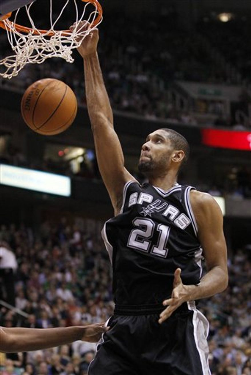 San Antonio Spurs center Tim Duncan (21) dunks the ball against the Utah jazz during the first half of an NBA basketball game in Salt Lake City, Friday, Nov. 19, 2010. Duncan scored 19 points in the Spurs' 94-82 win. (AP Photo/Colin E Braley)