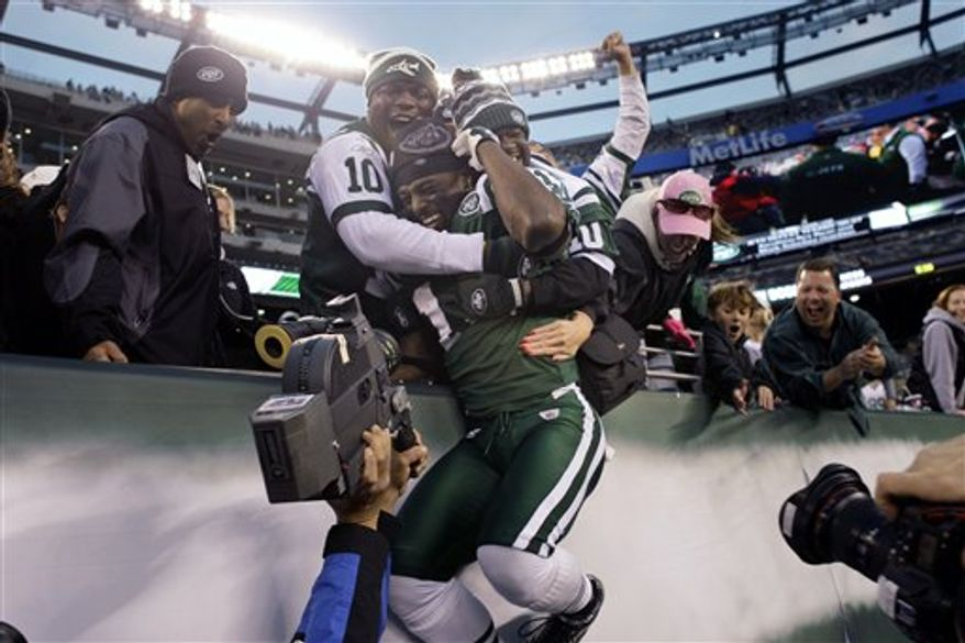 New York Jets Brad Smith (16) celebrates with quarterback Mark Sanchez (6) after Sanchez threw a touchdown-pass to win an NFL football game during the fourth quarter against the Houston Texans at New Meadowlands Stadium, Sunday, Nov. 21, 2010, in East Rutherford, N.J. The Jets won the game 30-27. (AP Photo/Frank Franklin II)