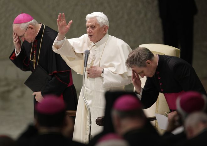 Pope Benedict XVI delivers his blessing, flanked by his personal aide Rev. Georg Gaenswein, right, and Archbishop James Harvey, Prefect of the Papal Household, during his weekly general audience, in Paul VI Hall, at the Vatican, Wednesday, Nov. 24, 2010. The Vatican on Wednesday denounced China for ordaining a bishop without papal consent, accusing the government-backed church of gravely damaging the faith, and warning that the bishop himself risked excommunication. (AP Photo/Andrew Medichini)