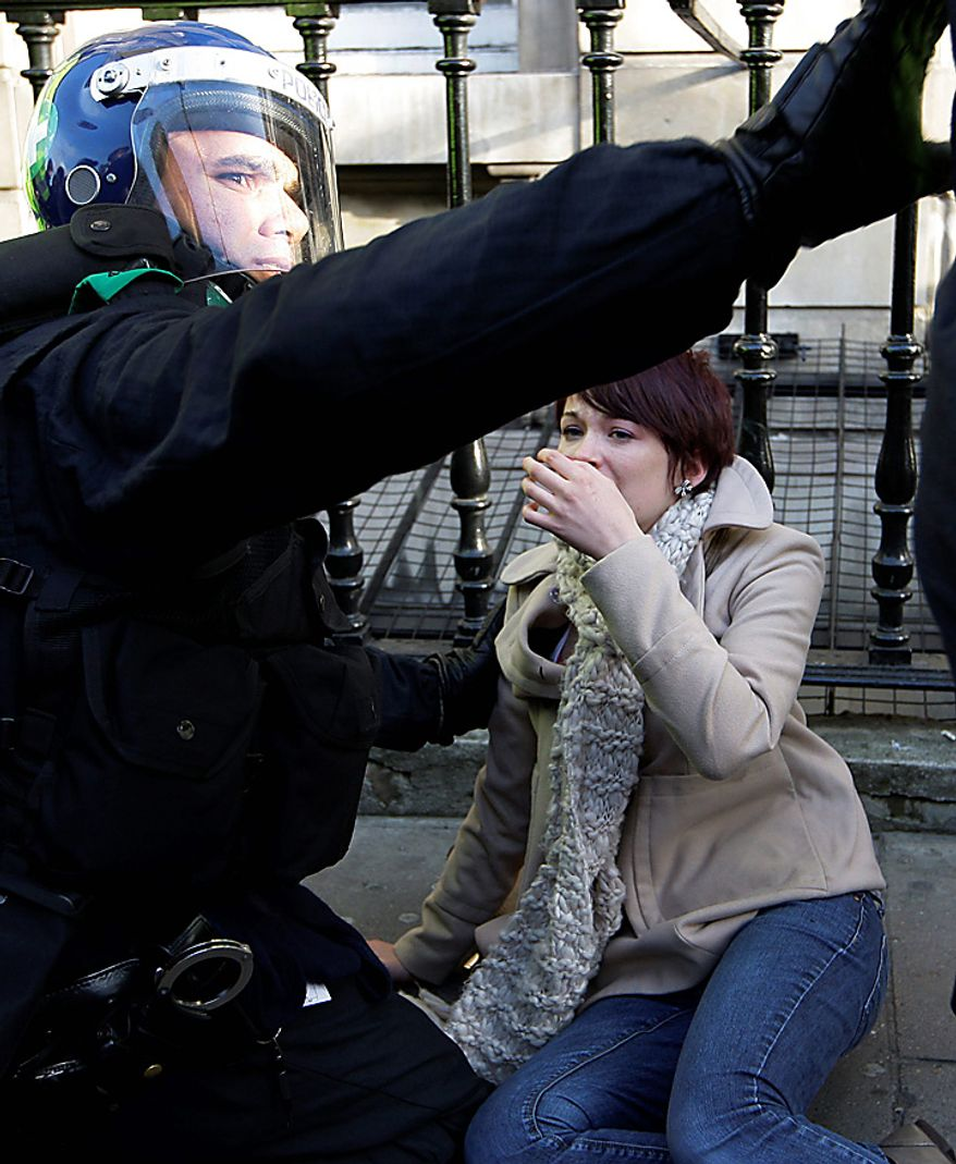 An injured protester is treated by police medic as thousands of students protest against tuition fees at Whitehall in London, Wednesday, Nov. 24, 2010. (AP Photo/Sang Tan)