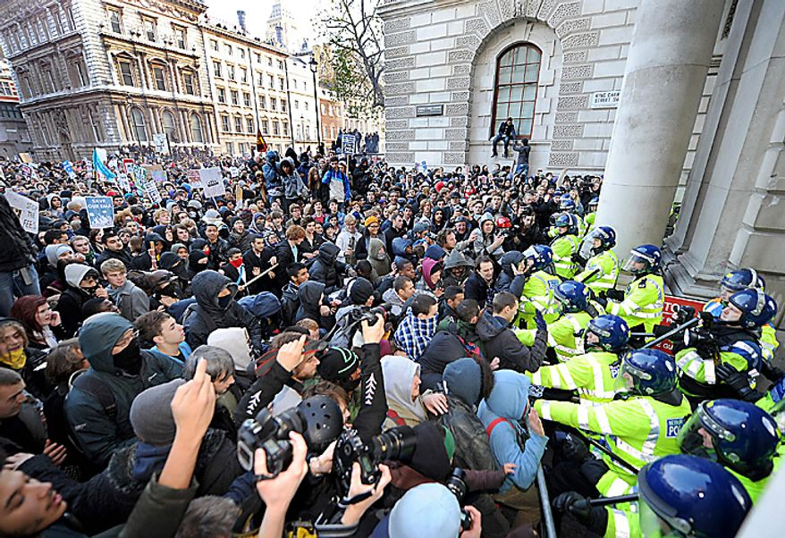 Student protesters clash with police during a demonstration against an increase in university tuition fees, in Westminster, central London, Wednesday Nov. 24, 2010. Several thousand British students protested Wednesday against government plans to triple tuition fees, two weeks after a similar demonstration sparked a small riot.  (AP Photo/Anthony Devlin/PA)