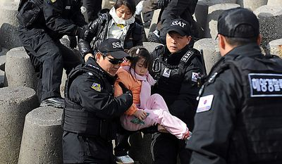 In this photo released by Korea Coast Guard, its members evacuate residents from Yeonpyeong island, South Korea, Wednesday, Nov. 24, 2010.  South Korea found the burned bodies Wednesday of two islanders killed in a North Korean artillery attack, marking the first civilian deaths in the incident and dramatically escalating the tensions in the region's latest crisis. (AP Photo/Korea Coast Guard, Ko Jae-young)