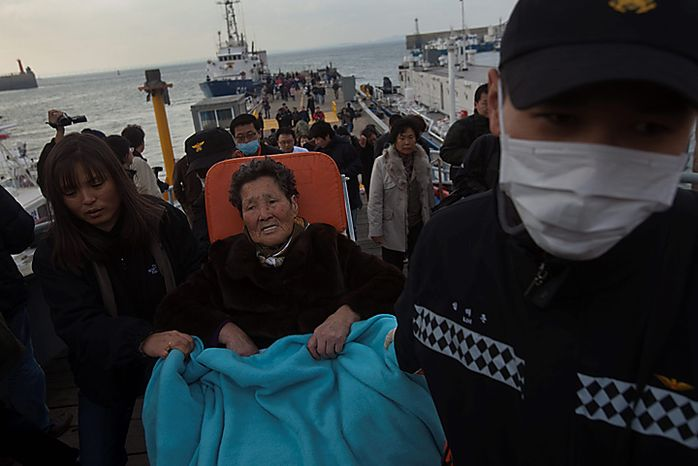 South Korean coast guard help people to disembark from a ship at a port in Incheon, South Korea after they were evacuated from Yeonpyeong Island,  Wednesday, Nov. 24, 2010. South Korea's troops were on high alert Wednesday as their government exchanged threats with rival North Korea following a frightening military skirmish that ratcheted tensions on the peninsula to new extremes. (AP Photo/David Guttenfelder)