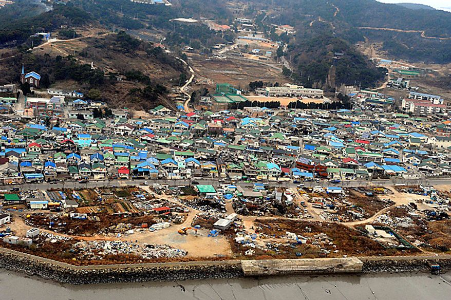 Destroyed houses are seen on South Korea's Yeonpyeong Island on Wednesday, Nov. 24, 2010. South Korea found the burned bodies of two islanders killed in a North Korean artillery attack, marking the first civilian deaths in the incident and dramatically escalating the tensions in the region's latest crisis. (AP Photo/Yonhap, Kim Hyun-tae)