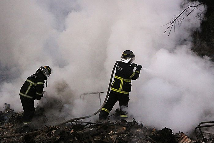 South Korean firefighters extinguish a fire at a house on Yeonpyeong island, South Korea, Wednesday, Nov. 24, 2010. South Korea says it has found the burnt bodies of two islanders killed in a North Korean artillery attack, marking the first two civilian deaths in the crisis and escalating tensions between the rival Koreas. (AP Photo/Yonhap)