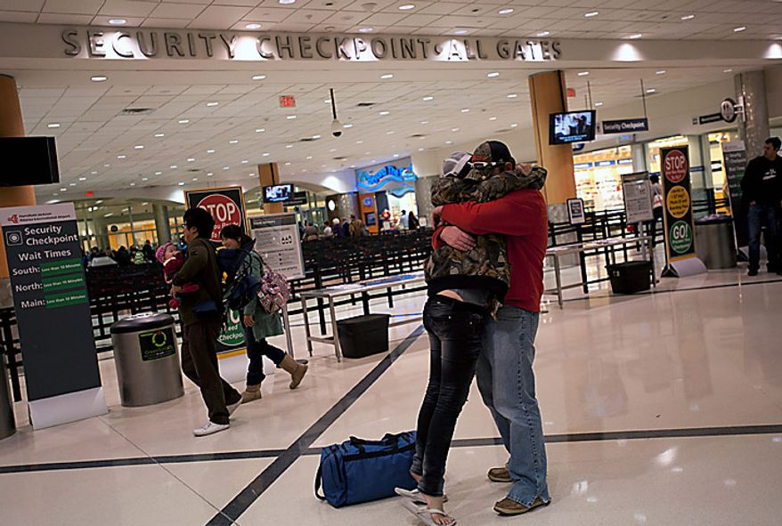 "Samantha Steiner, left, and Kenneth McGrotha embrace in front of the security checpoint area at Hartsfield-Jackson International Airport in Atlanta, Georgia, U.S., on Wednesday, Nov. 24, 2010. Atlanta's Hartsfield-Jackson International Airport, the world's busiest and the biggest hub for Delta Air Lines Inc., has seen ""no operational impact"" from passengers objecting to body scans, said John Kennedy, a spokesman. Photographer: Chris Rank/Bloomberg"