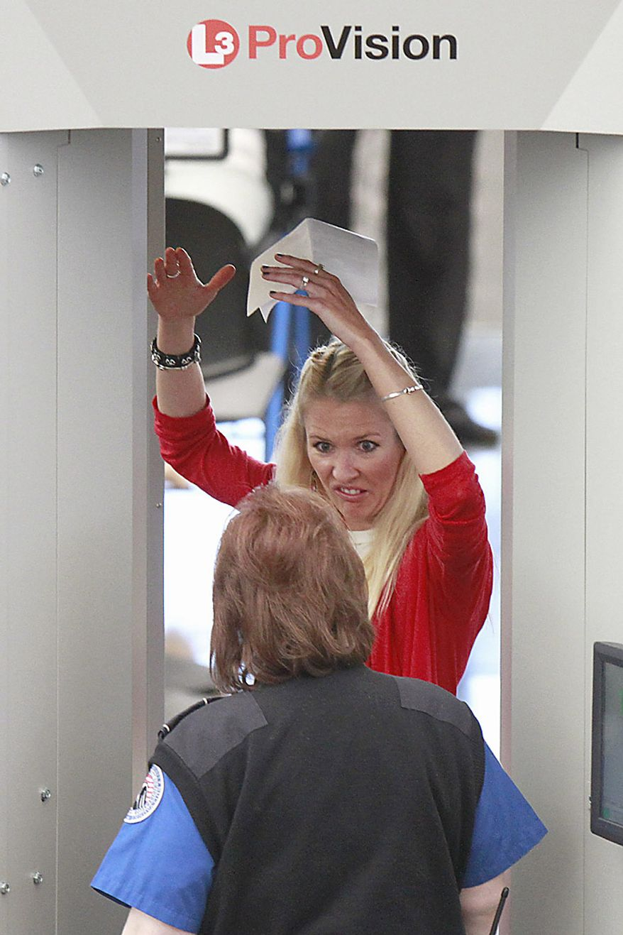 A woman reacts to a TSA agent while having her body scanned during the busiest travel weekend of the year at Denver International Airport, Wednesday, Nov. 24, 2010. (AP Photo/Barry Gutierrez)