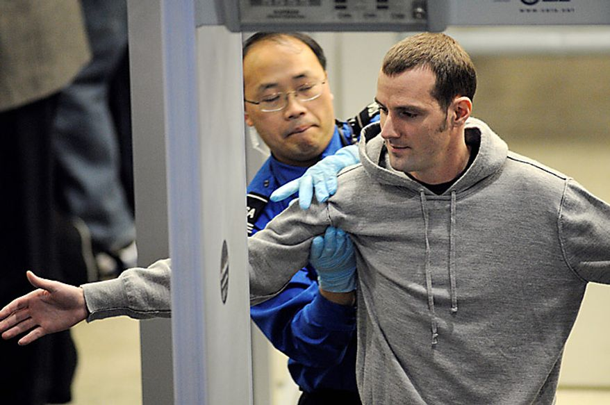 ** FILE ** Transportation Security Administration (TSA) officer pats down a traveler as he works his way through security at the Minneapolis-St. Paul International Airport in Bloomington, Minn. (AP Photo/Craig Lassig)