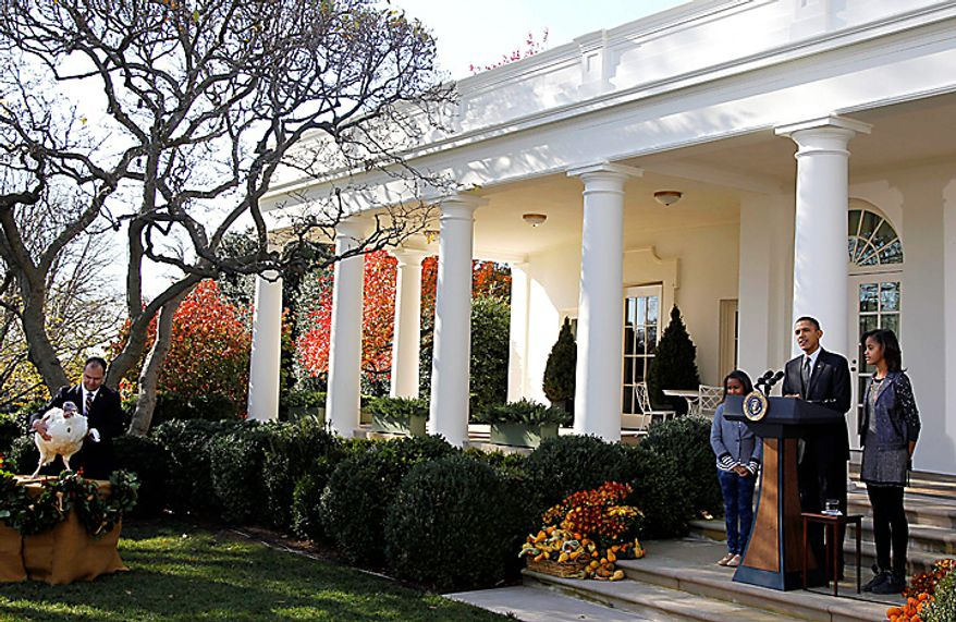 President Barack Obama, stands with daughters Malia Obama and Sasha Obama as he pardoned Apple, the National Thanksgiving Turkey, during a ceremony in the Rose Garden of the White House in Washington, Wednesday, Nov. 24, 2010. At left is National Turkey Federation Chairman Yubert Envia. (AP Photo/Charles Dharapak)