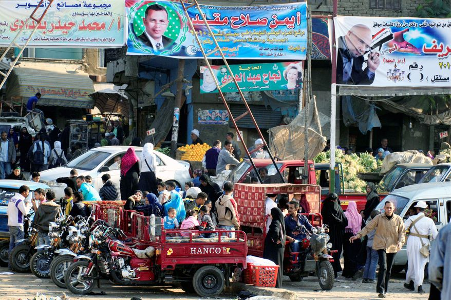 """Election banners in Cairo depict candidates in parliamentary elections scheduled for this weekend. A U.S. State Department spokesman said that a U.S. request for independent election monitors """"is not interfering in Egyptian affairs."""" (Associated Press)"""