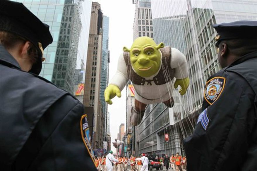 Members of the New York Police Department stand by as the Shrek balloon makes it's way across 42nd Street during the Macy's Thanksgiving Day Parade on Thursday, Nov. 25, 2010 in New York. (AP Photo/Tina Fineberg)