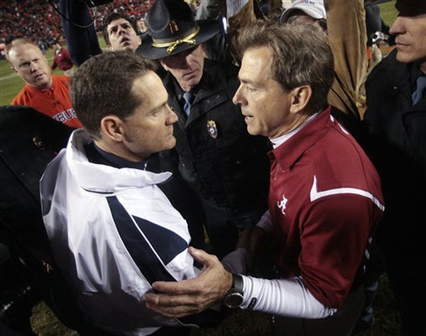 FILE - In this Nov. 27, 2009, file photo, Auburn coach Gene Chizik, left, greets Alabama coach Nick Saban after Alabama beat Auburn 26-21 in an NCAA college football game at Jordan-Hare Stadium in Auburn, Ala. It is cliche to say this Southeastern Conference rivalry divides families--it's also true. Alabama-Auburn is a 365-days-a-year topic in the state. How important is this game? Put it this way, if Alabama beats Auburn on Friday but somehow the Tigers still went on to win the national championship, there will be plenty of Tide fans convinced their team had the better season. (AP Photo/Dave Martin, File)