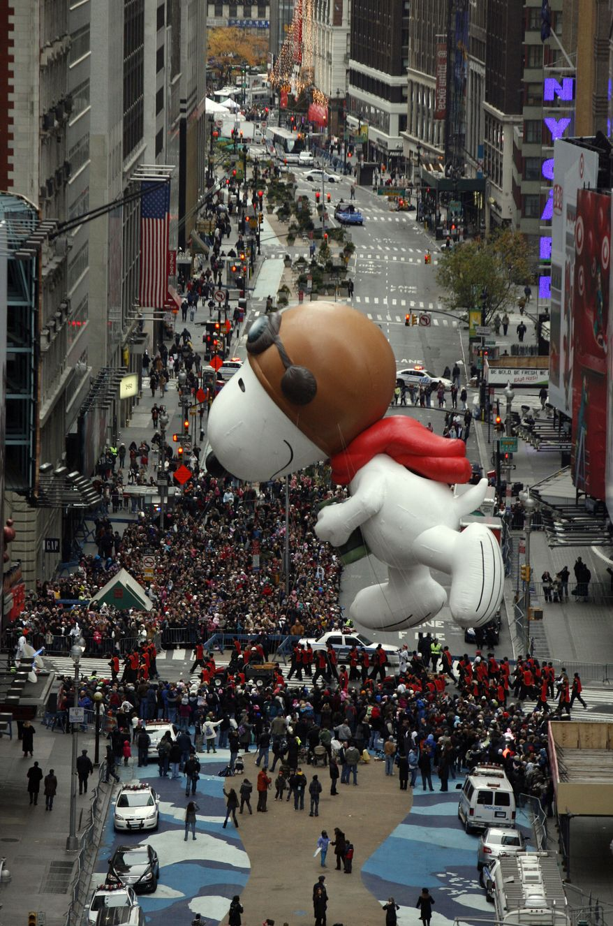 The Snoopy balloon floats through Times Square during the Macy's Thanksgiving Day parade in New York, Thursday, Nov. 25, 2010. (AP Photo/Jeff Christensen)