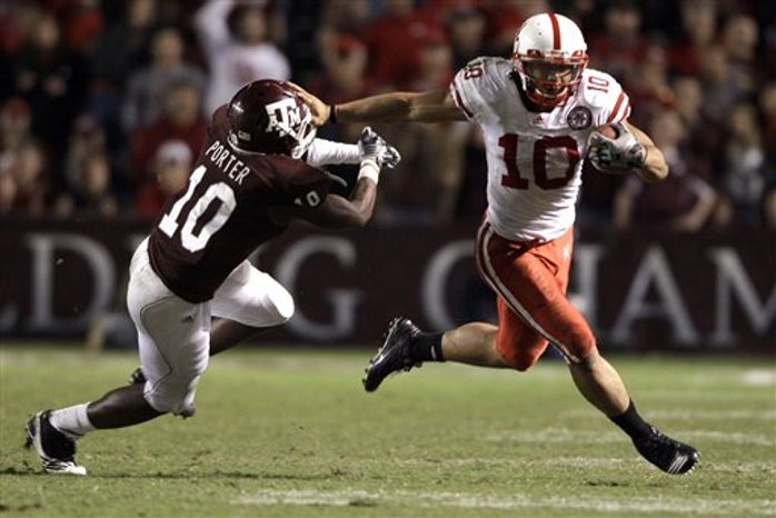Nebraska quarterback Taylor Martinez (3) rushes for a first down as Texas A&M cornerback Terrence Frederick (7) defends during the first quarter of an NCAA college football game Saturday, Nov. 20, 2010, in College Station, Texas. (AP Photo/David J. Phillip)