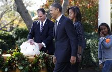 President Obama walks with daughters Malia and Sasha after he pardoned Apple, the National Thanksgiving Turkey, during a ceremony in the Rose Garden of the White House in Washington, Wednesday, Nov. 24, 2010. At rear is National Turkey Federation Chairman Yubert Envia. (AP Photo/Charles Dharapak)