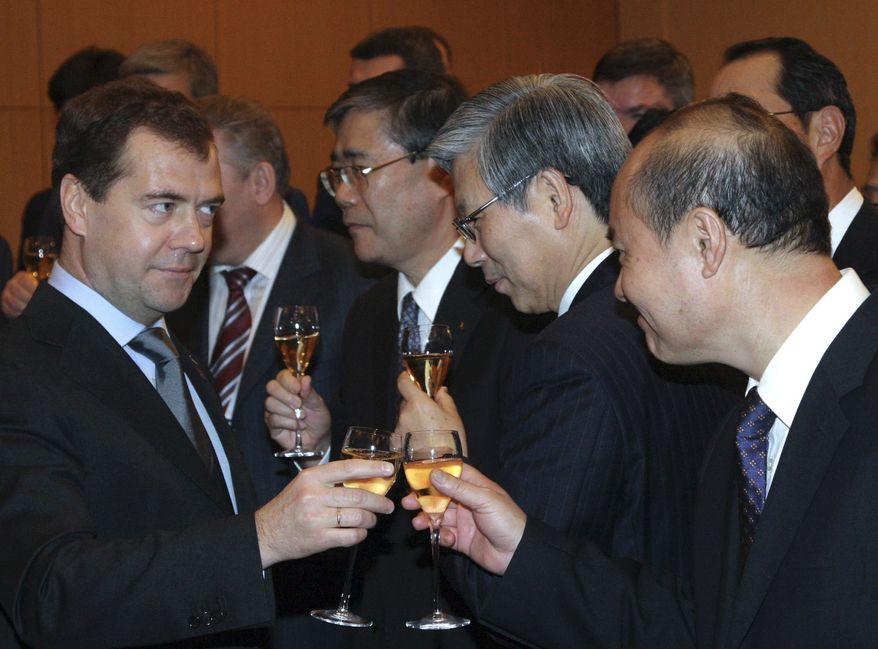 ** FILE ** Russian President Dmitry Medvedev, left, clinks glasses with officials during a signing of trilateral agreement before the opening of the APEC summit in Yokohama, Japan, on Saturday, Nov. 13, 2010. Russia, Japan and China signed an agreement to build a chemical plant in Tatarstan, Russia. (AP Photo/RIA Novosti, Mikhail Klimentyev, Presidential Press Service)
