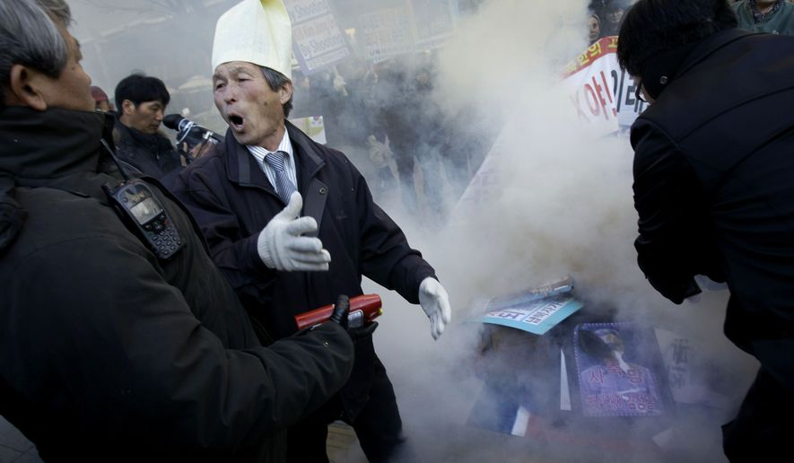 An anti-North Korea protester threatens police trying to extinguish burning icons of North Korea during a demonstration on Friday, Nov. 26, 2010, in Seoul, South Korea. Fresh artillery shots were heard Friday on the tense South Korean island of Yeonpyeong, three days after it was devastated by a North Korean attack and hours after Pyongyang warned that the peninsula was on the brink of war. (AP Photo/Wally Santana)