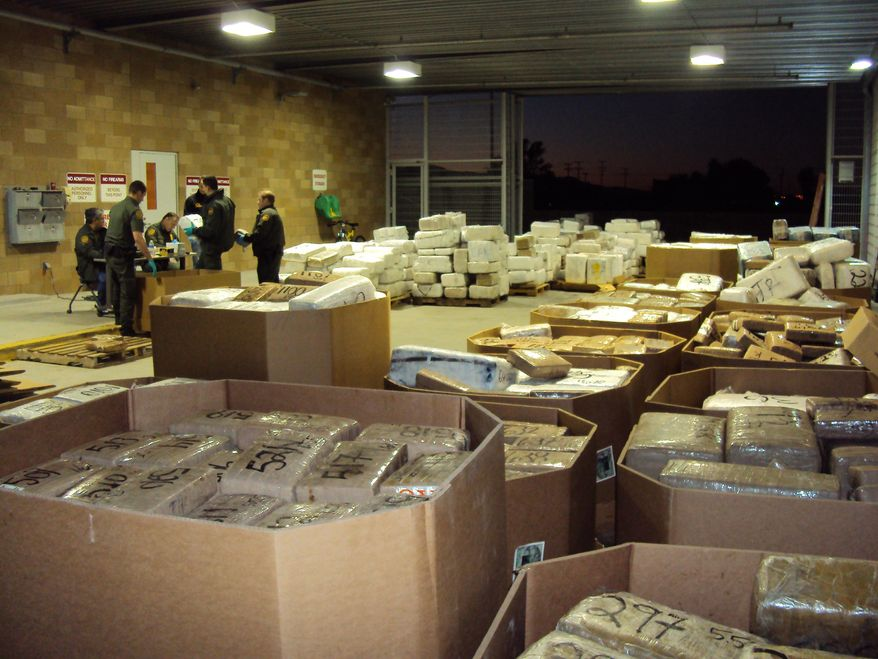In this Nov. 25, 2010, photo released by U.S. Immigration and Customs Enforcement (ICE), packages of seized marijuana are examined by officials in Murrieta, Calif., after a cross-border tunnel between Tijuana, Mexico and San Diego was discovered. (AP Photo/U.S. Immigration and Customs Enforcement)