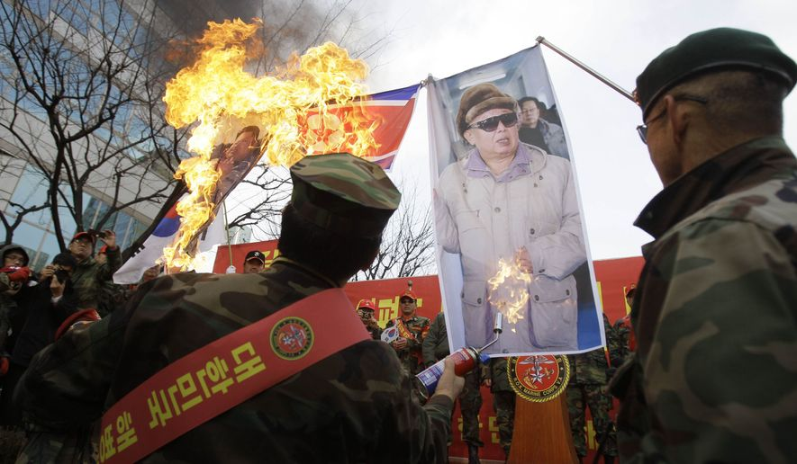 Former South Korean marines burn images of North Korean leader Kim Jong il, right, and his son Kim Jong Un, during a rally denouncing North Korea on Saturday, Nov. 27, 2010, in Seoul, South Korea. South Korea is gearing up for joint military maneuvers with the U.S. starting Sunday that are likely to keep tensions soaring following the attack on a South Korean island, which killed two two marines and two civilians. (AP Photo/Wally Santana)