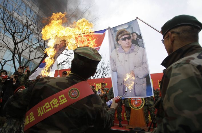 Former South Korean marines burn images of North Korean leader Kim Jong il, right, and his son Kim Jong Un, during a rally denouncing North Korea on Saturday, Nov. 27, 2010, in Seoul, South Korea. South Korea is gearing up for joint military maneuvers with the U.S. starting Sunday that are likely to keep tensions soaring followi