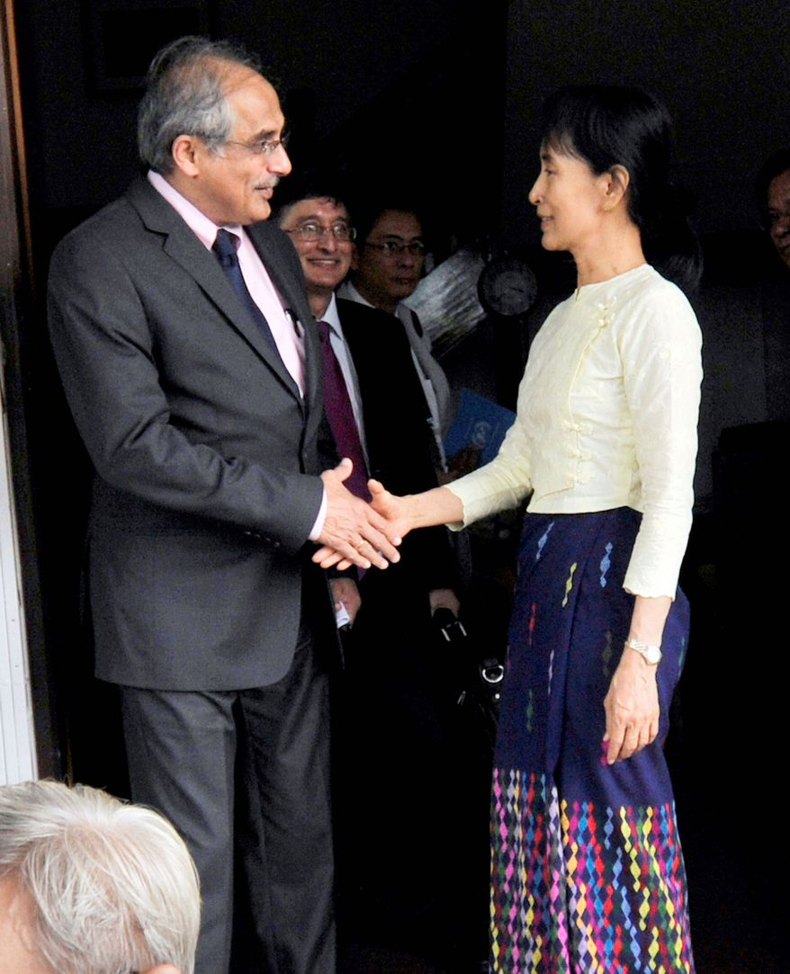 Myanmar's pro-democracy leader, Aung San Suu Kyi, shakes hands with Vijay Nambiar, chief of staff for U.N. Secretary-General Ban Ki-moon, after their meeting at her home on Saturday in Yangon, Myanmar. Mrs. Suu Kyi met for more than an hour with Mr. Nambiar and said she hopes the talks will be the first of many with the world body to solve the country's problems. (Associated Press)