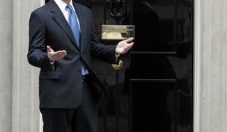 British Prime Minister David Cameron, standing outside his official residence at 10 Downing Street in central London, greets Sweden's Prime Minister Frank Reinfeldt, not seen, prior to their meeting, Thursday Nov. 25, 2010. (AP Photo/Lefteris Pitarakis)