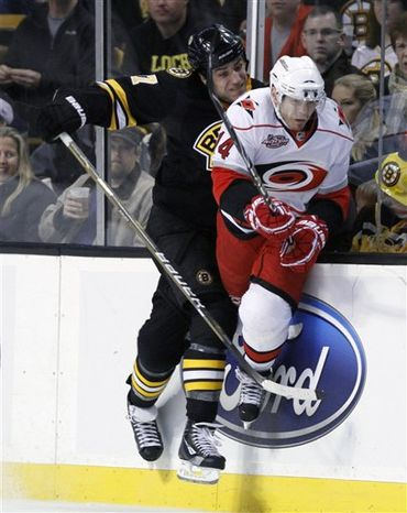 Carolina Hurricanes' Jeff Skinner, foreground, scores past Boston Bruins' Tim Thomas, right, in the first period of an NHL hockey game, Friday, Nov. 26, 2010, in Boston. (AP Photo/Michael Dwyer)