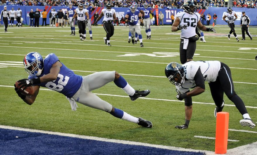 New York Giants' Mario Manningham, left, scores a touchdown during the fourth quarter of the NFL football game against the Jacksonville Jaguars at New Meadowlands Stadium, Sunday, Nov. 28, 2010, in East Rutherford, N.J. (AP Photo/Bill Kostroun)