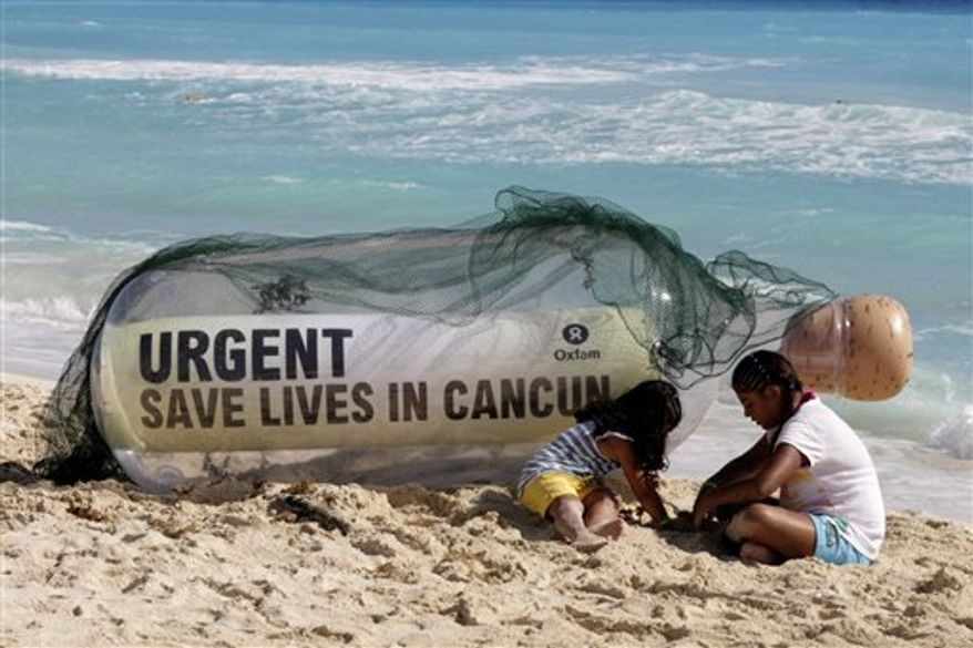 People walk past a sand sculpture made by activists of Oxfam, a group of non-governmental organizations, during the United Nations Climate Change Conference in Cancun, Mexico, Friday, Dec. 10, 2010. (AP Photo/Israel Leal)