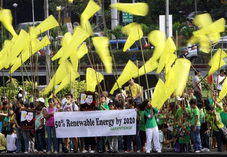 Greenpeace activists wave windsocks as they campaign for the use of renewable energy Saturday, Nov. 27, 2010 in Pasay City, south of Manila, Philippines. The Filipino activists called on President Benigno Aquino III to commit to 50 percent renewable energy by 2020 as one of the solutions to fight climate change. (AP Photo/Pat Roque)