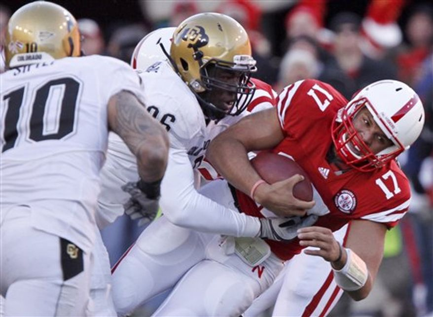Colorado defensive end Chidera Uzo-Diribe (96) tackles Nebraska quarterback Cody Green (17) as Colorado linebacker Michael Sipili (10) moves in during the first half of their NCAA college football game, in Lincoln, Neb., Friday, Nov. 26, 2010. (AP Photo/Nati Harnik)