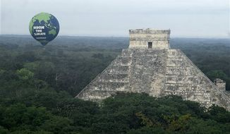 In this image released by Greenpeace on Sunday Nov. 28, 2010, a  giant balloon rises next to the Chichen-Itza pyramids in Mexico's Yucatan peninsula, Sunday Nov. 28, 2010.  Facing another year without a global deal to curb climate change, the world's nations will spend the next two weeks in Cancun, Mexico, during the annual conference of the 193-nation U.N. climate treaty, debating how to mobilize money to cope with what's coming, as temperatures climb, ice melts, seas rise and the climate that nurtured man shifts in unpredictable ways. (AP Photo/Greenpeace)