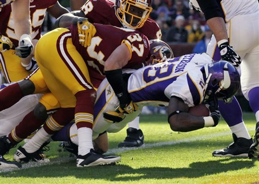 Minnesota Vikings running back Adrian Peterson (28) scores a touchdown as Washington Redskins safety Reed Doughty hangs on during the first half of an NFL football game in Landover, Md., Sunday, Nov. 28, 2010. (AP Photo/Pablo Martinez Monsivias)