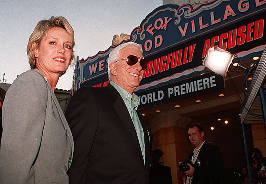 """In this file photo taken Aug. 19, 1998, Leslie Nielsen, center, and his wife Barbaree, left, pose for pictures at the premiere of his comedy movie """"Wrongfully Accused"""" in the Westwood area of Los Angeles. The Canadian-born Nielsen, who went from drama to inspired bumbling as a hapless doctor in """"Airplane!"""" and the accident-prone detective Frank Drebin in """"The Naked Gun"""" comedies, has died. He was 84. His agent John S. Kelly said Nielsen died Sunday, Nov. 28, 2010, at a hospital near his home in Florida where he was being treated for pneumonia. (AP Photo/Mark J. Terrill, File)"""